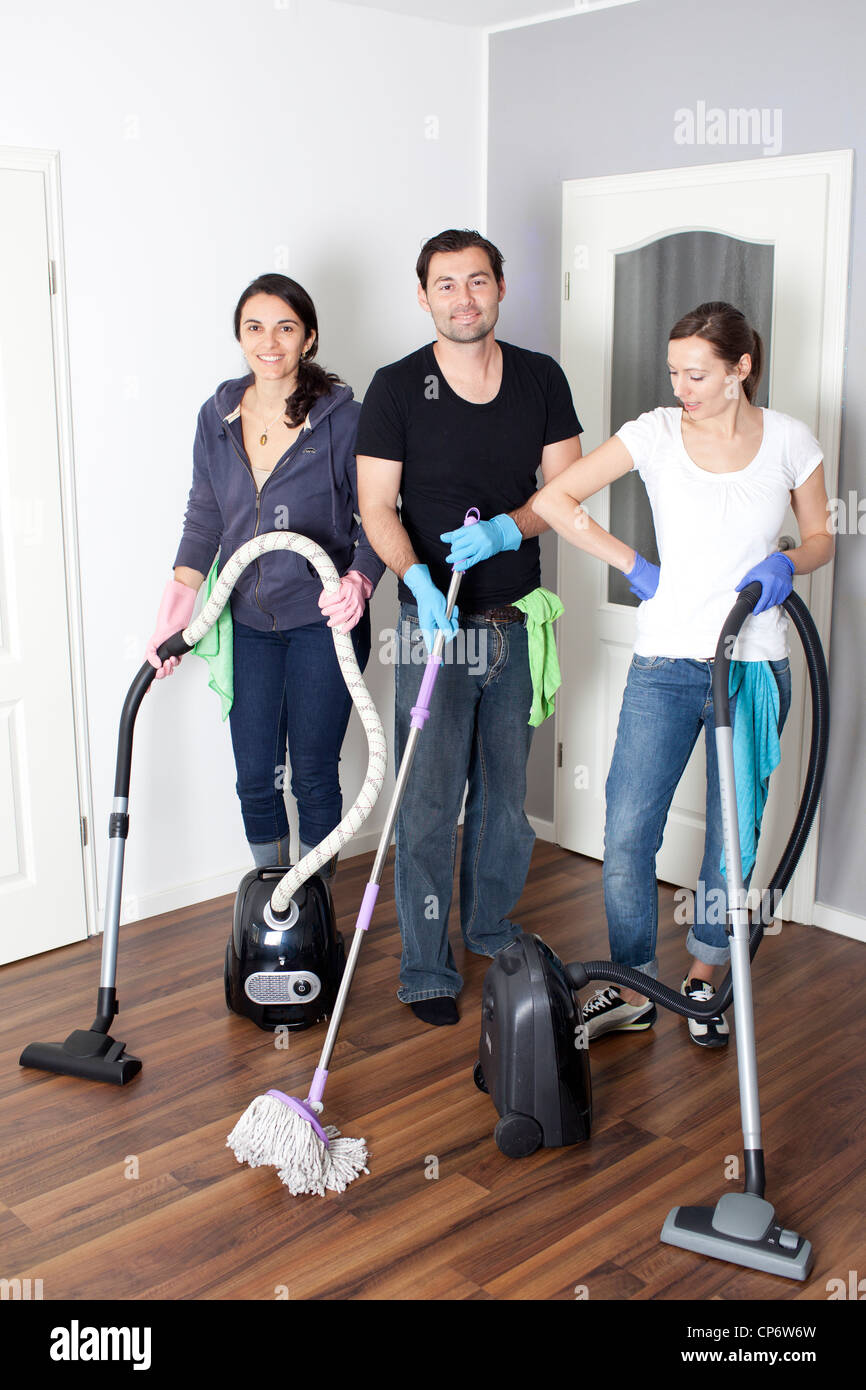 Three persons cleaning a house - Stock Image