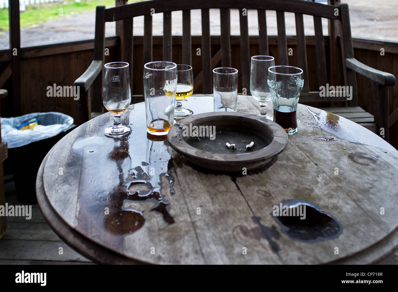 A pub table with ashtray and empty glasses - Stock Image