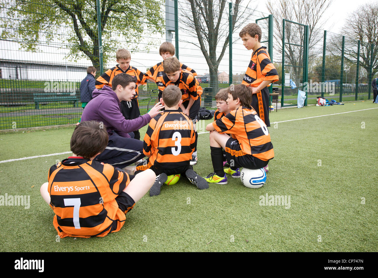 A coach talking tactics to team of young soccer players/footballers. - Stock Image