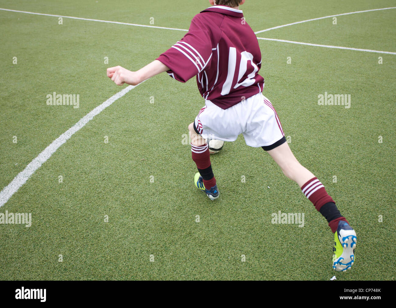 A young footballer about to kick a football. - Stock Image