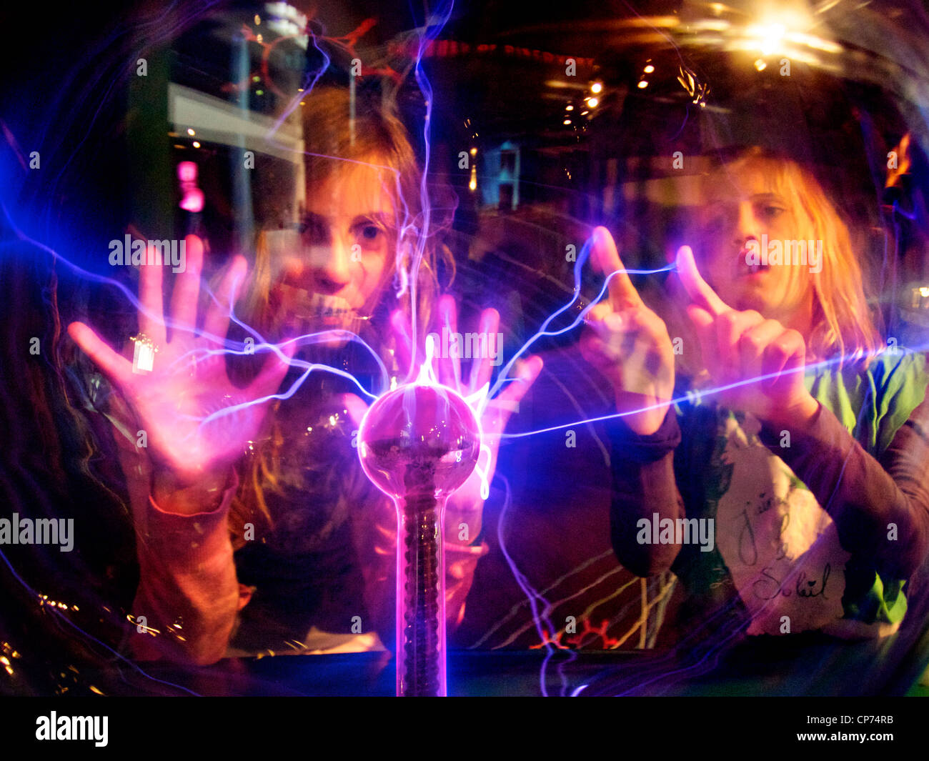 Girls 11 and 7 years old fascinated by tesla plasma ball, Tegelen, the Netherlands - Stock Image