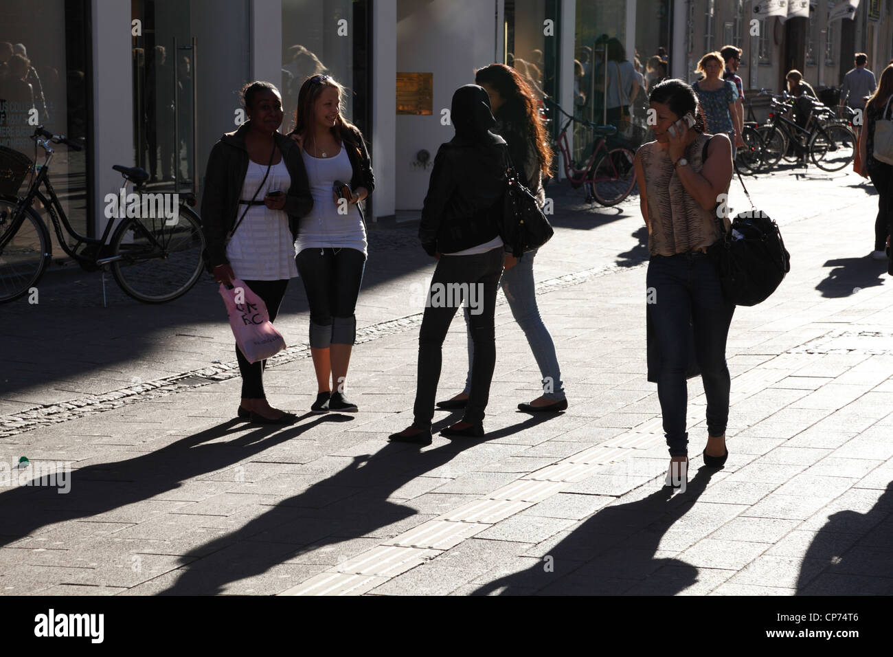 Girls and women on Strøget in Copenhagen late afternoon in backlight. Shopping and early entertaining on a - Stock Image