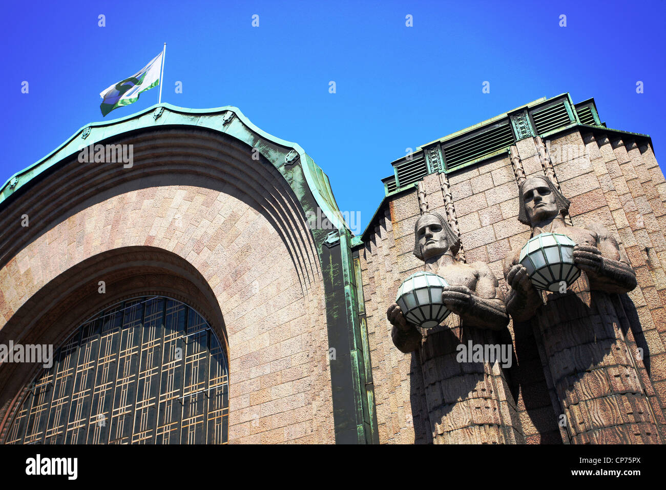 Imposing statues holding spherical lamps at the entrance to Helsinki Railway Station Finland - Stock Image