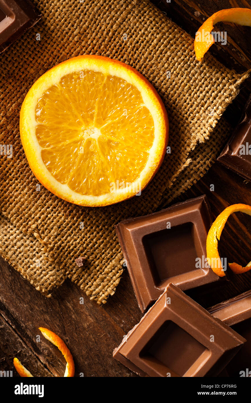 Orange Slice with Chocolate Squares on Jute and Wood - Stock Image