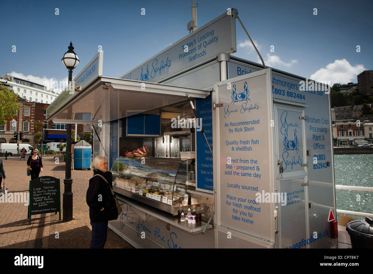 UK, England, Devon, Torquay Harbour, middle aged tourist at Browse seafoods quayside fish stall - Stock Image