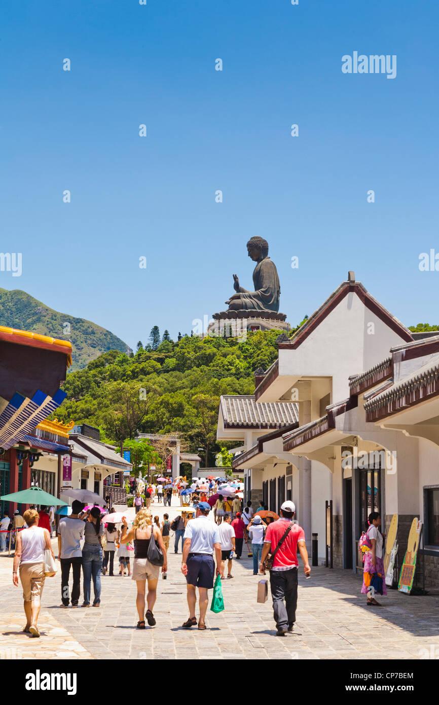 Visitors in the main street of Ngong Ping on Lantau Island, Hong Kong, dominated by the Tian Tan Buddha statue. - Stock Image