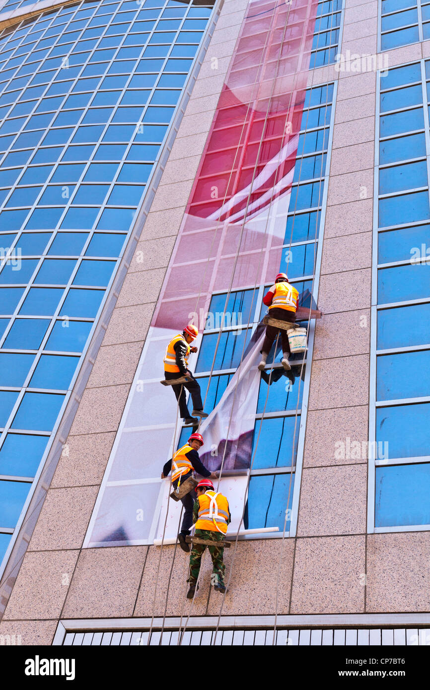 Workmen hanging a poster or billboard in sections on the side of a building in Wangfujing Street, Beijing, China - Stock Image