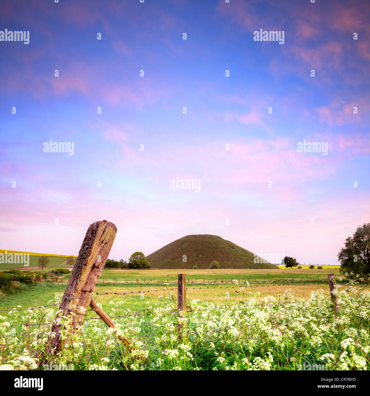 Silbury Hill, a Neolithic monument in Wiltshire, nearAvebury, on a beautiful spring morning with blue sky and pink - Stock Image