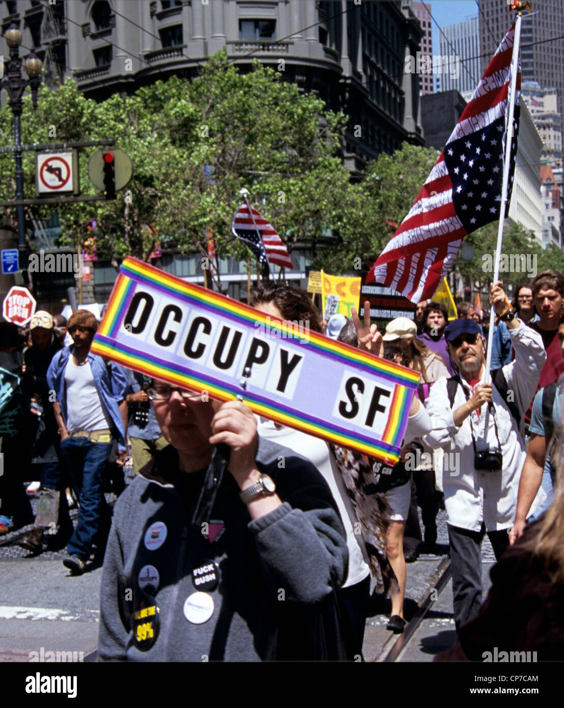 Occupy San Francisco marchers hold signs and upside down American flags protesting on May Day on market street - Stock Image