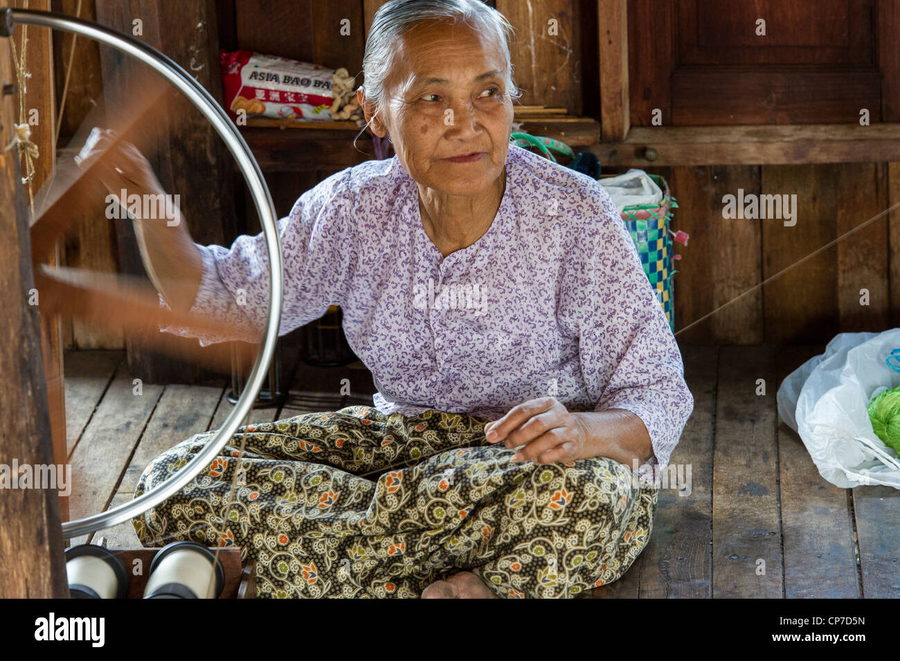 Woman working on a spinning wheel, Inle Lake, Myanmar Stock Photo