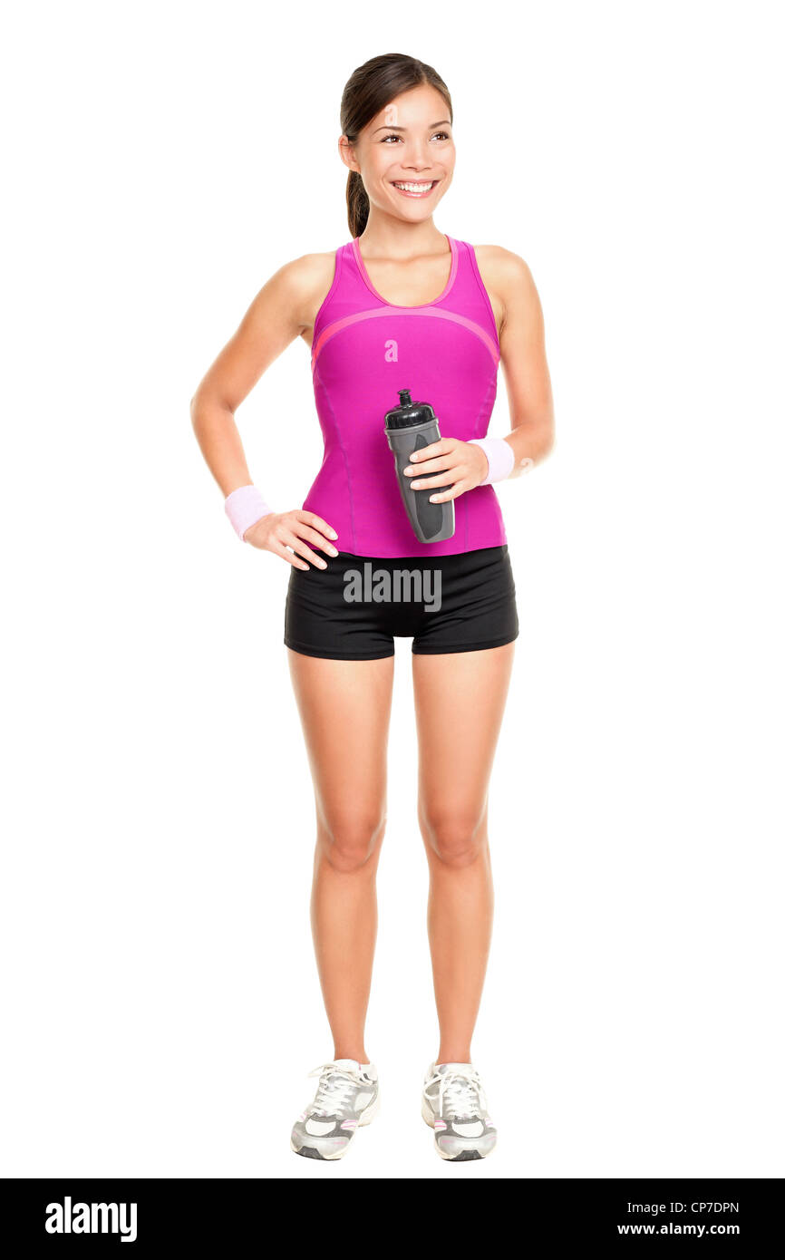 Full length of fit young multiracial Asian Caucasian woman in sporty gym clothing holding water bottle on white - Stock Image