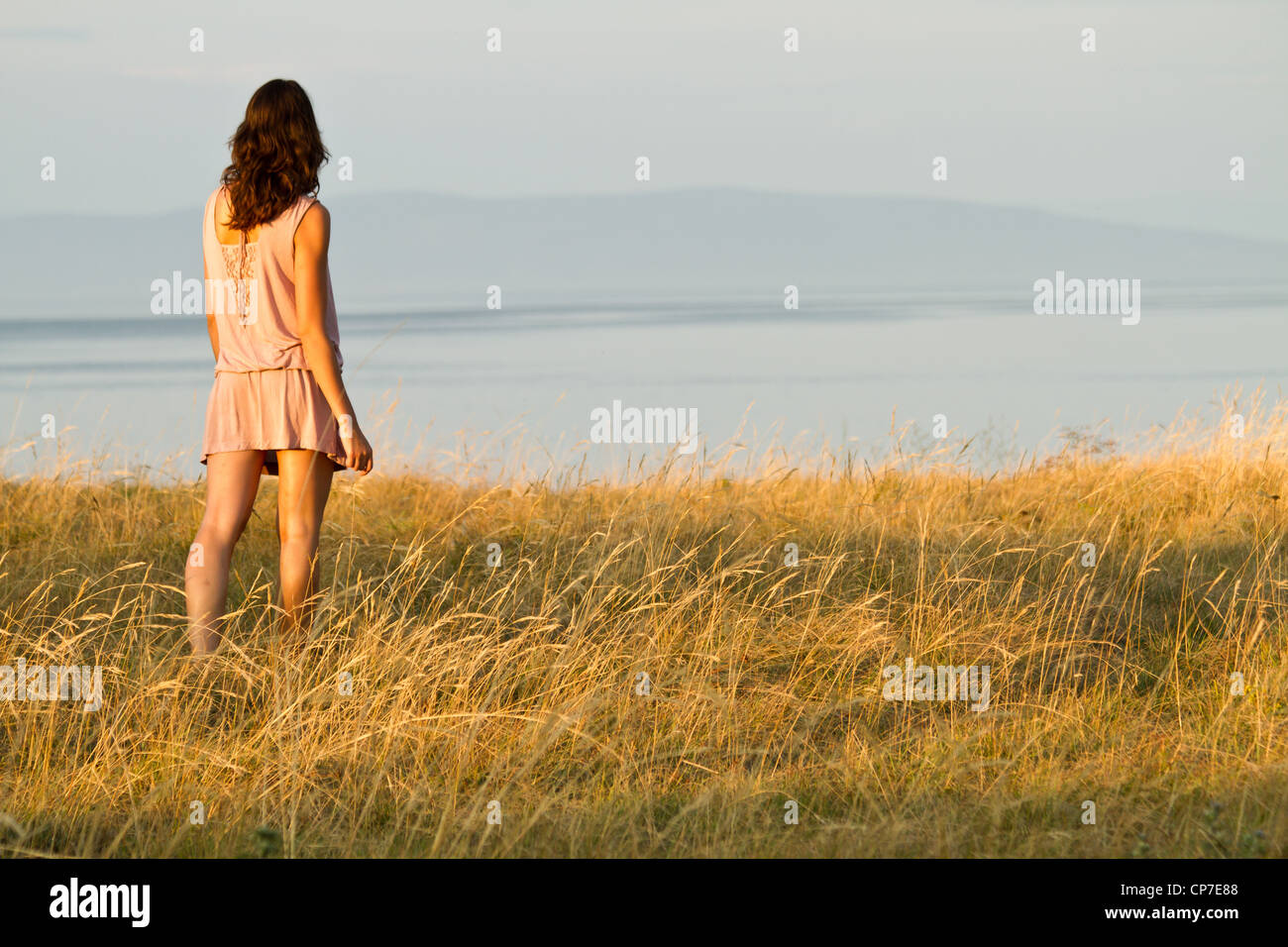 young woman in dress looking to the sea - Stock Image