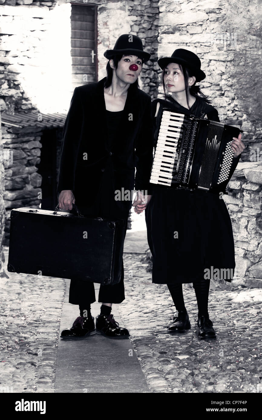 a couple of clowns is walking through an old, narrow street, the man has an old suitcase, the woman plays the accordion - Stock Image