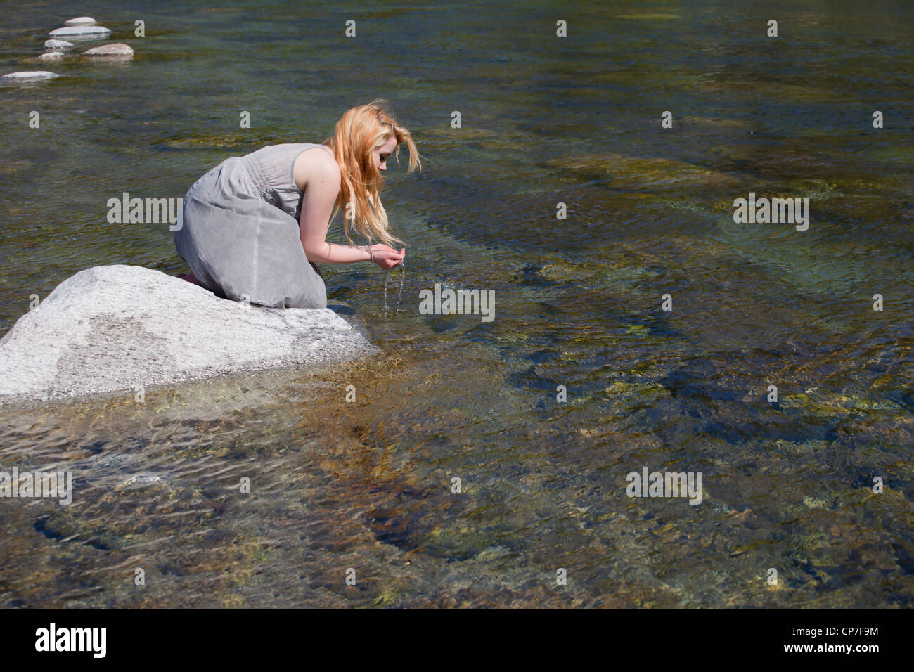 young woman sitting on a rock in a river and drinks water out of the hands - Stock Image