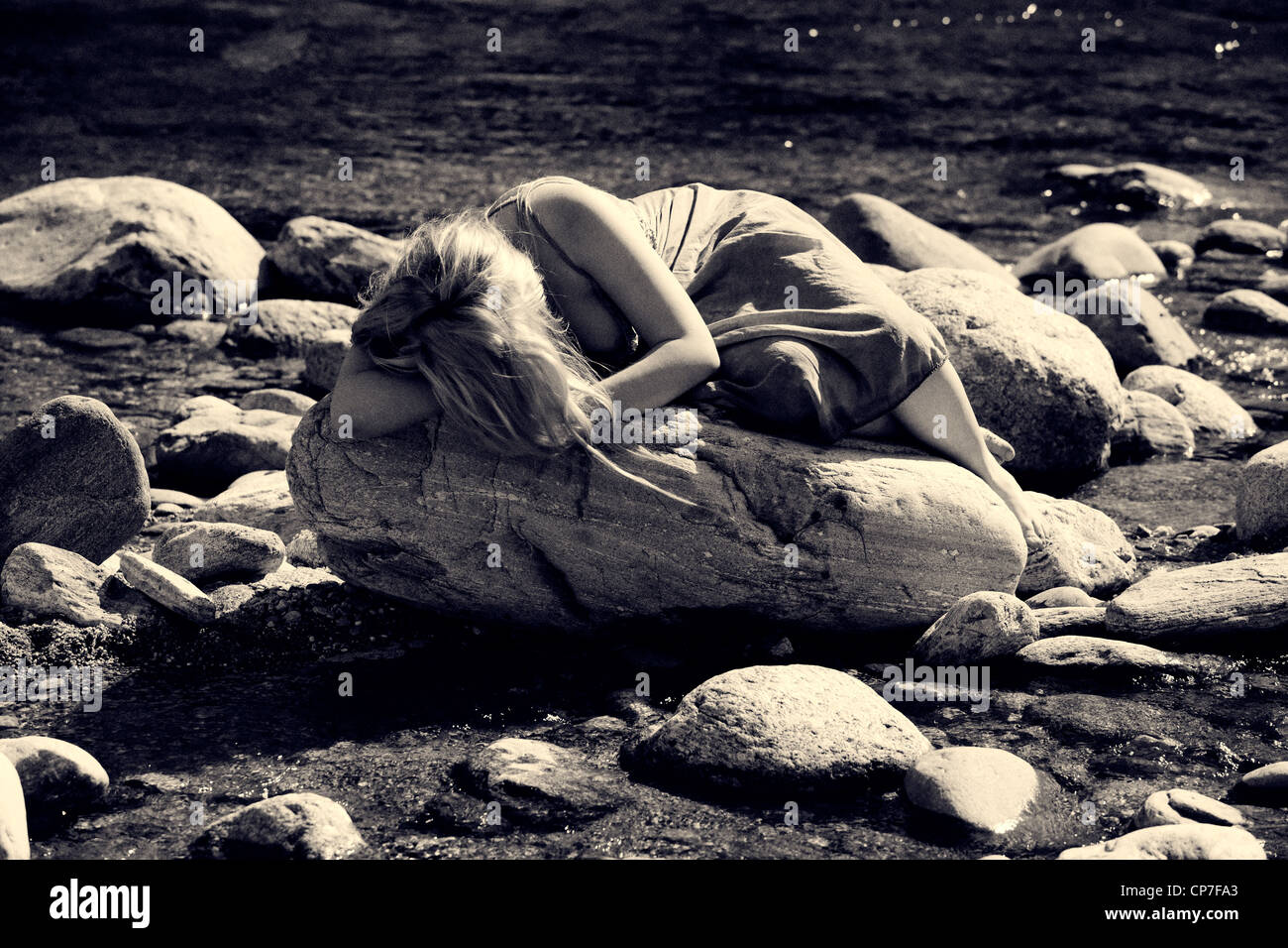 young woman lying on a rock in a river - Stock Image