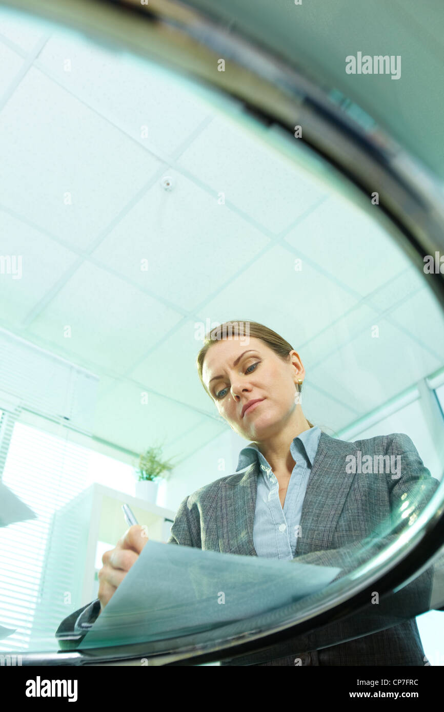Vertical shot of business woman viewed from below the glassy table Stock Photo