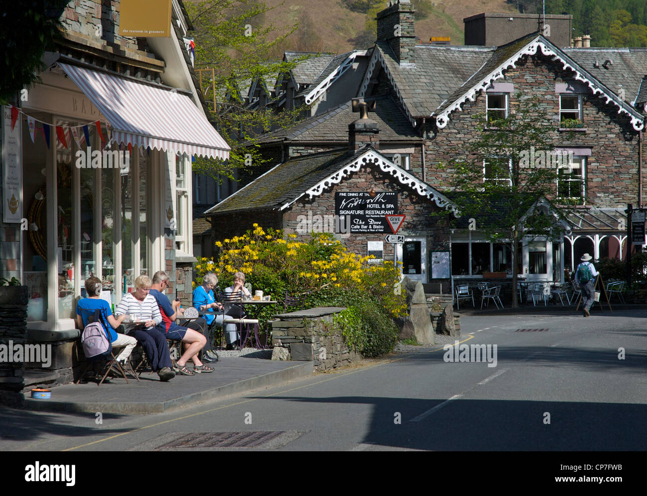 People sitting outside tearoom, in the village of Grasmere, Lake District National Park, Cumbria, England UK - Stock Image