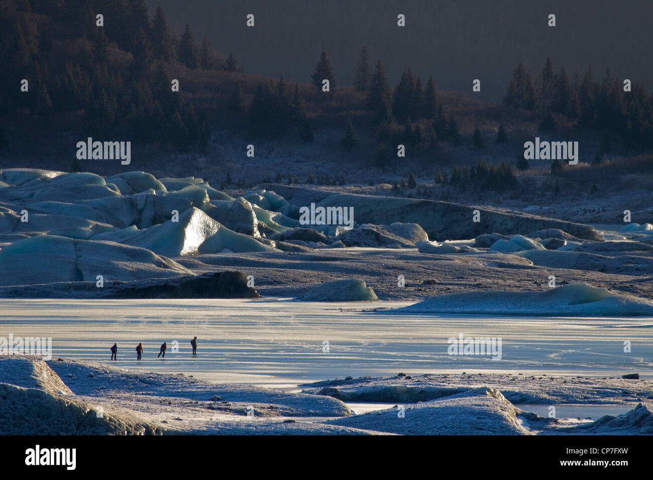 Family of ice skaters near Sheridan Glacier with icebergs in the background, Cordova, Southcentral Alaska, Winter - Stock Image