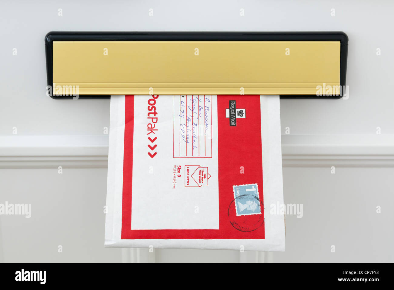 UK Royal Mail PostPak envelope with a large letter first class stamp posted through a letterbox flap in a white door at home. England Britain