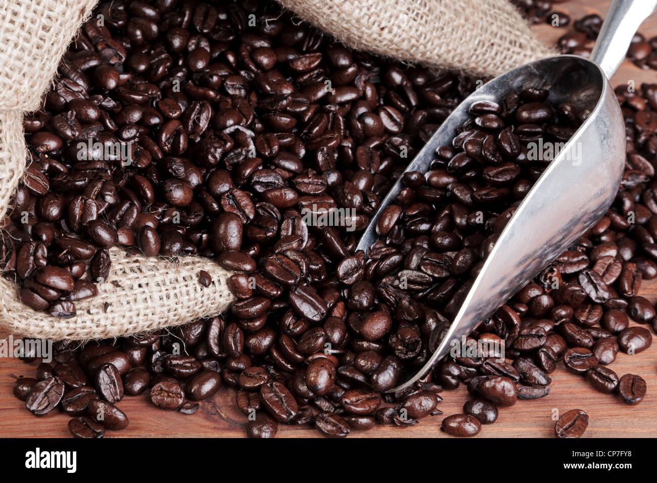 Photo of coffee beans in a hessian sack with metal scoop - Stock Image