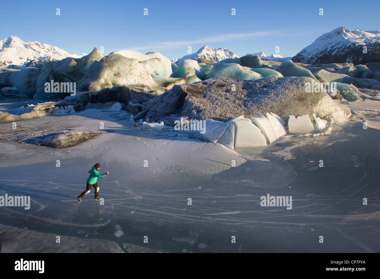 Woman ice skating among broken icebergs of Sheridan Glacier, Chugach Mountains near Cordova, Southcentral Alaska, - Stock Image