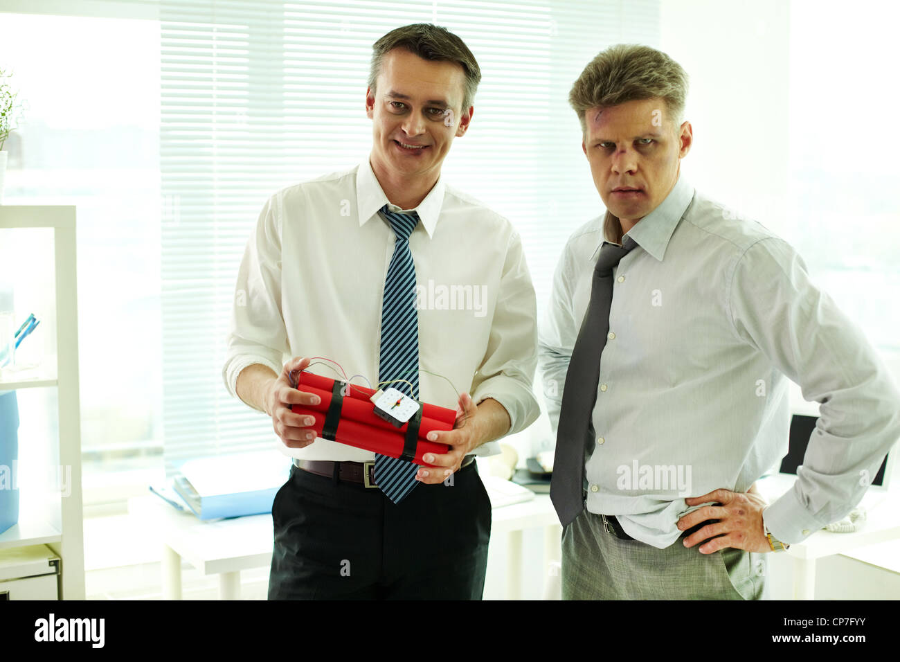 Portrait of two businessmen with bruised faces looking at camera, one of them holding bomb - Stock Image