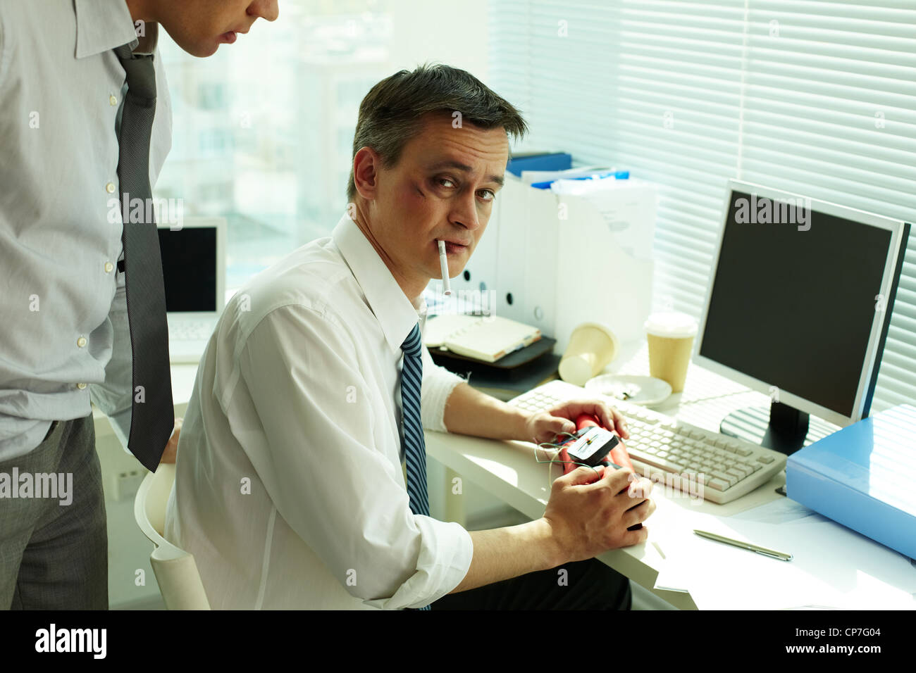 Portrait of businessman with bruised face and cigarette holding dynamite and looking at camera - Stock Image