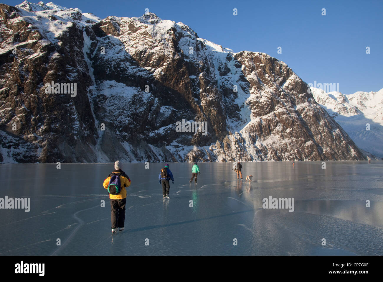 Group of ice skaters on Saddlebag Lake, Chugach Mountains near Cordova, Southcentral Alaska, Winter - Stock Image