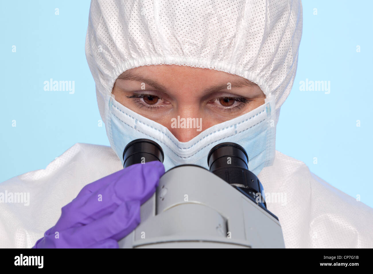 Photo of a biochemist looking through the eyepieces of a stereo optical laboratory microscope. - Stock Image