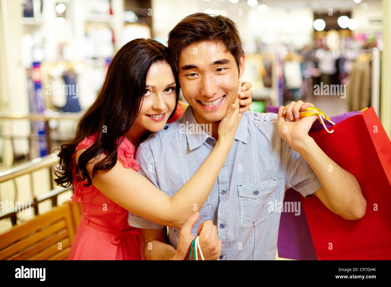 Beautiful girl hugging tenderly her boyfriend with shopping bags - Stock Image