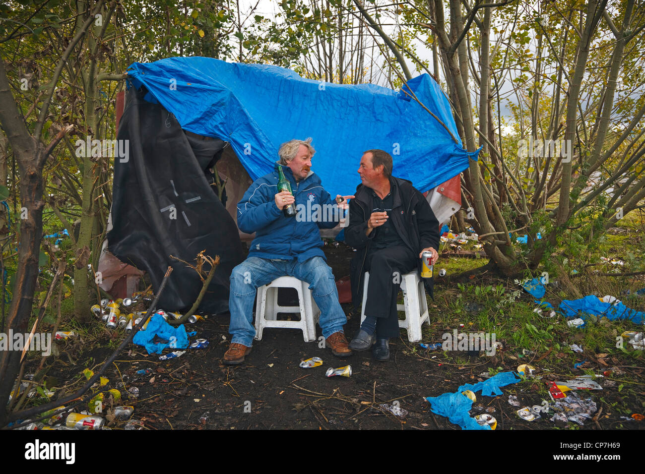 Two 'down and outs' drinking cheap wine and lager living in a makeshift tent in a disused Clyde dockyard, - Stock Image