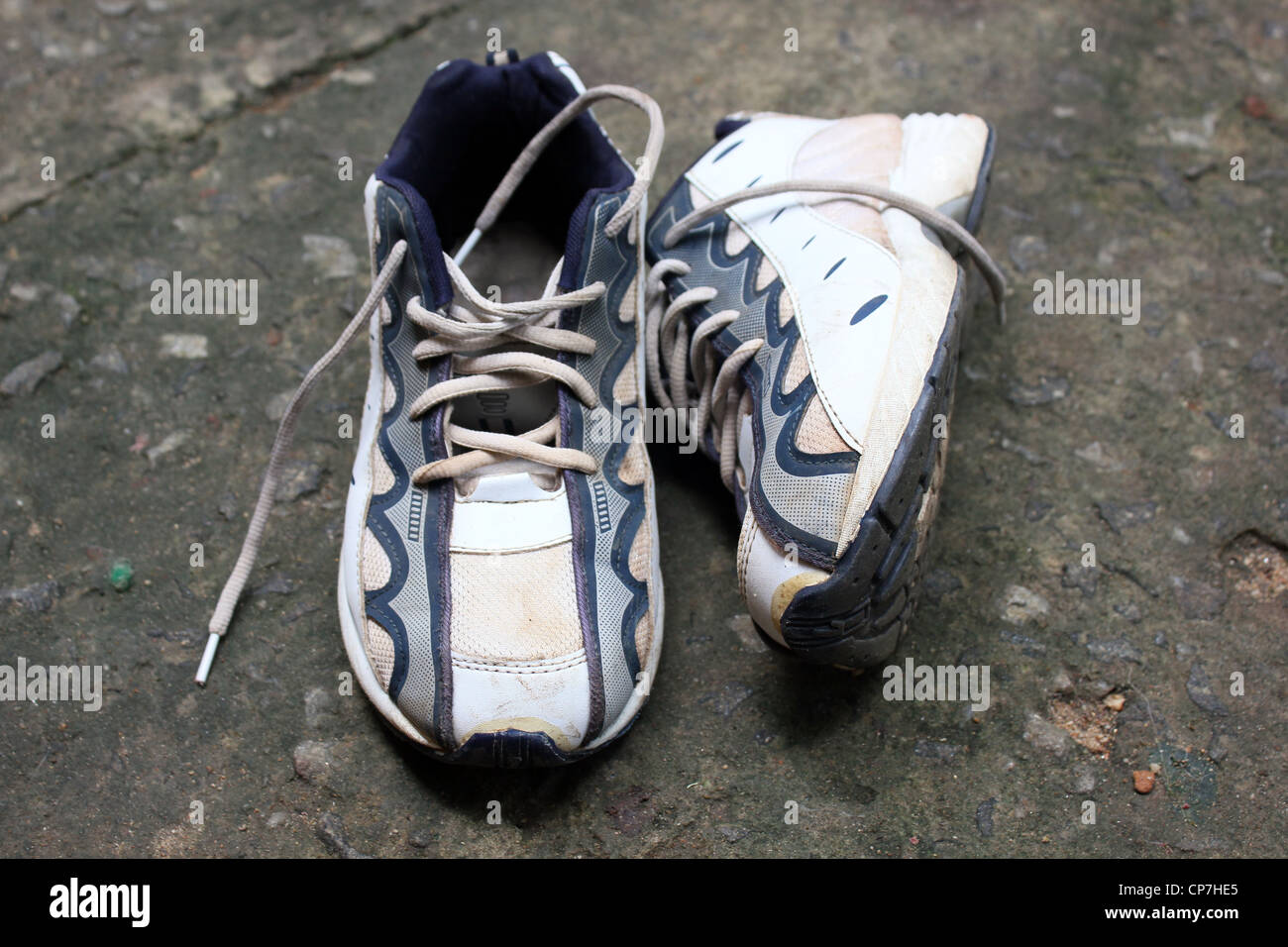 A pair of old white canvas shoes - Stock Image