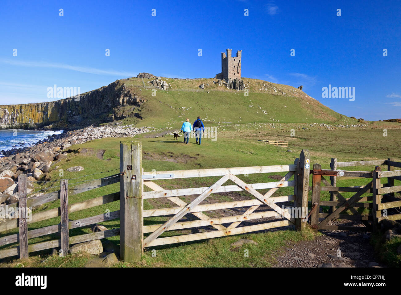Man and woman walking on the English Coastal Walking route at Dunstanburgh Castle, Northumberland, England, UK, - Stock Image
