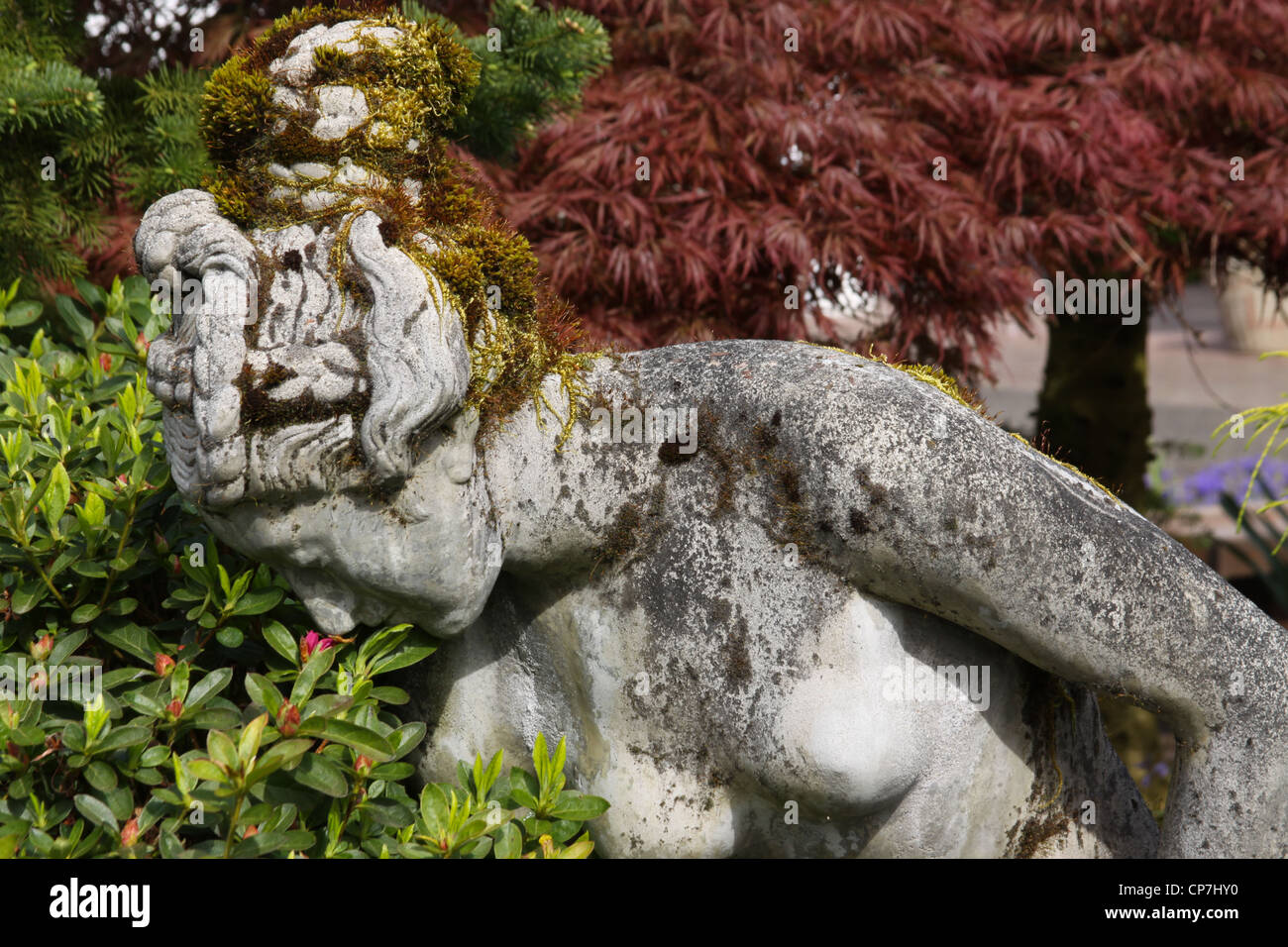 The statue in the garden takes time to smell  the flowers. - Stock Image