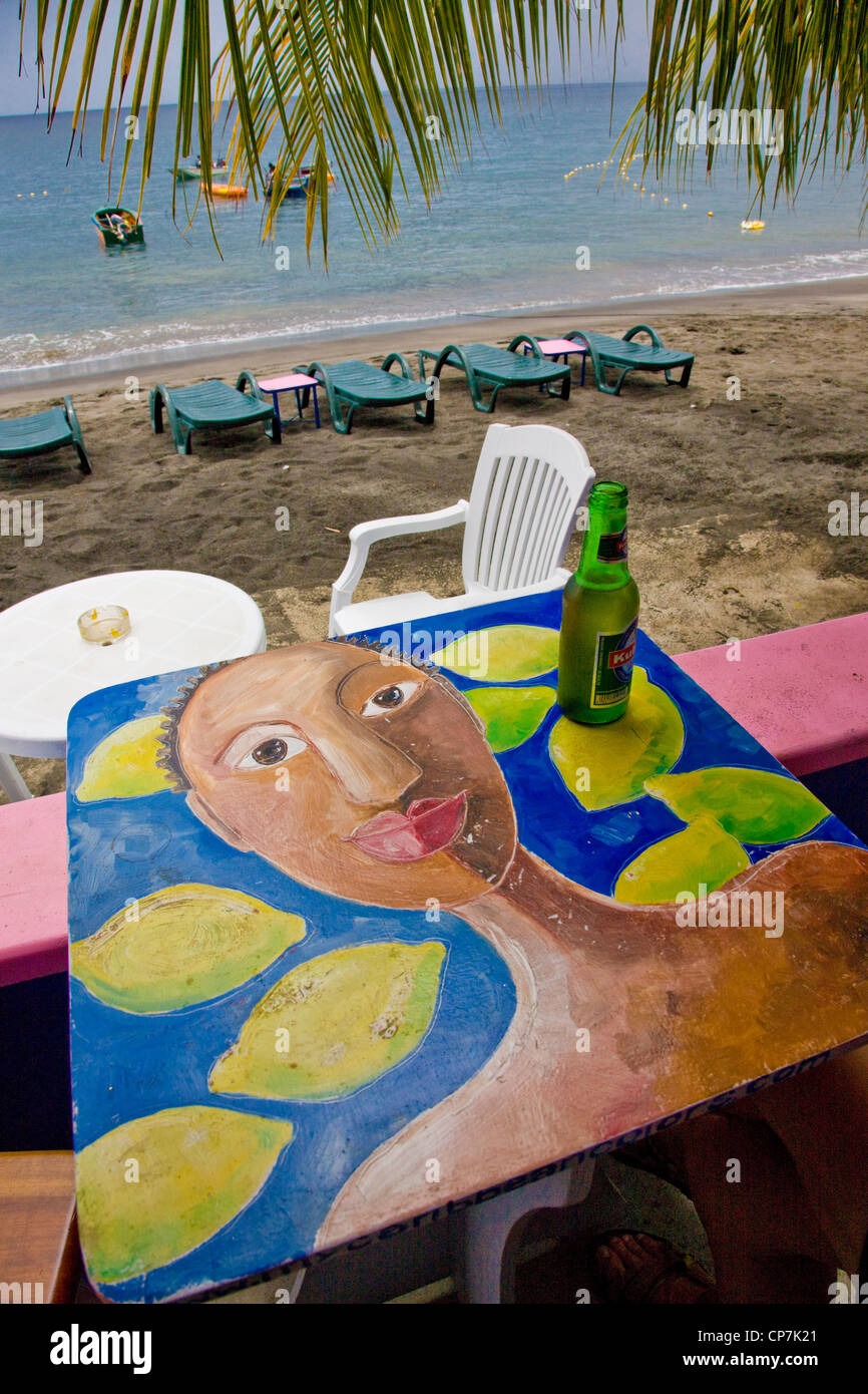 Painted table featuring a stylised woman and lemons in a beachside cafe in Mero Western Dominica in the West Indies - Stock Image