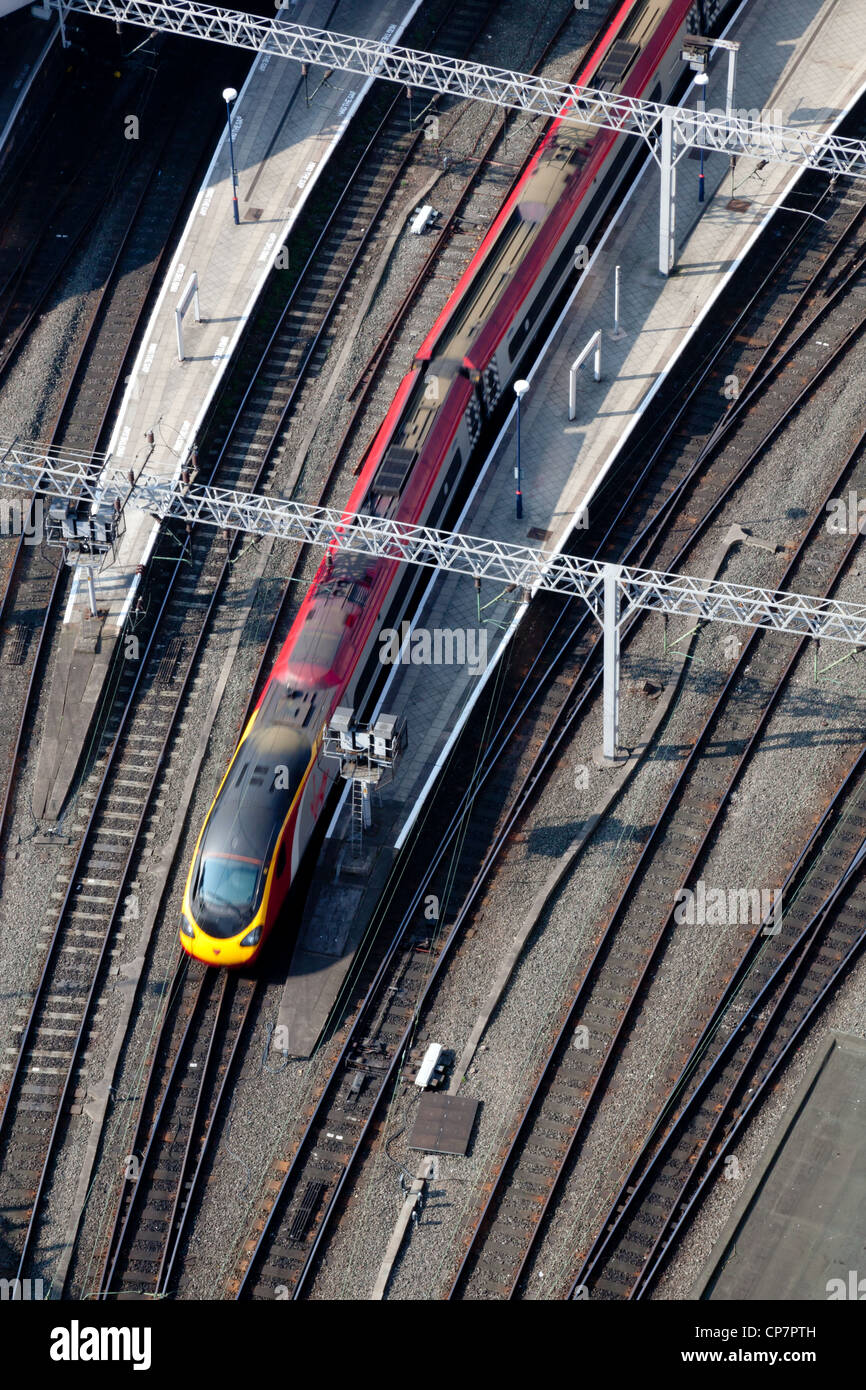 Bird's eye view of a train approaching a station, sidelit in the morning light. - Stock Image