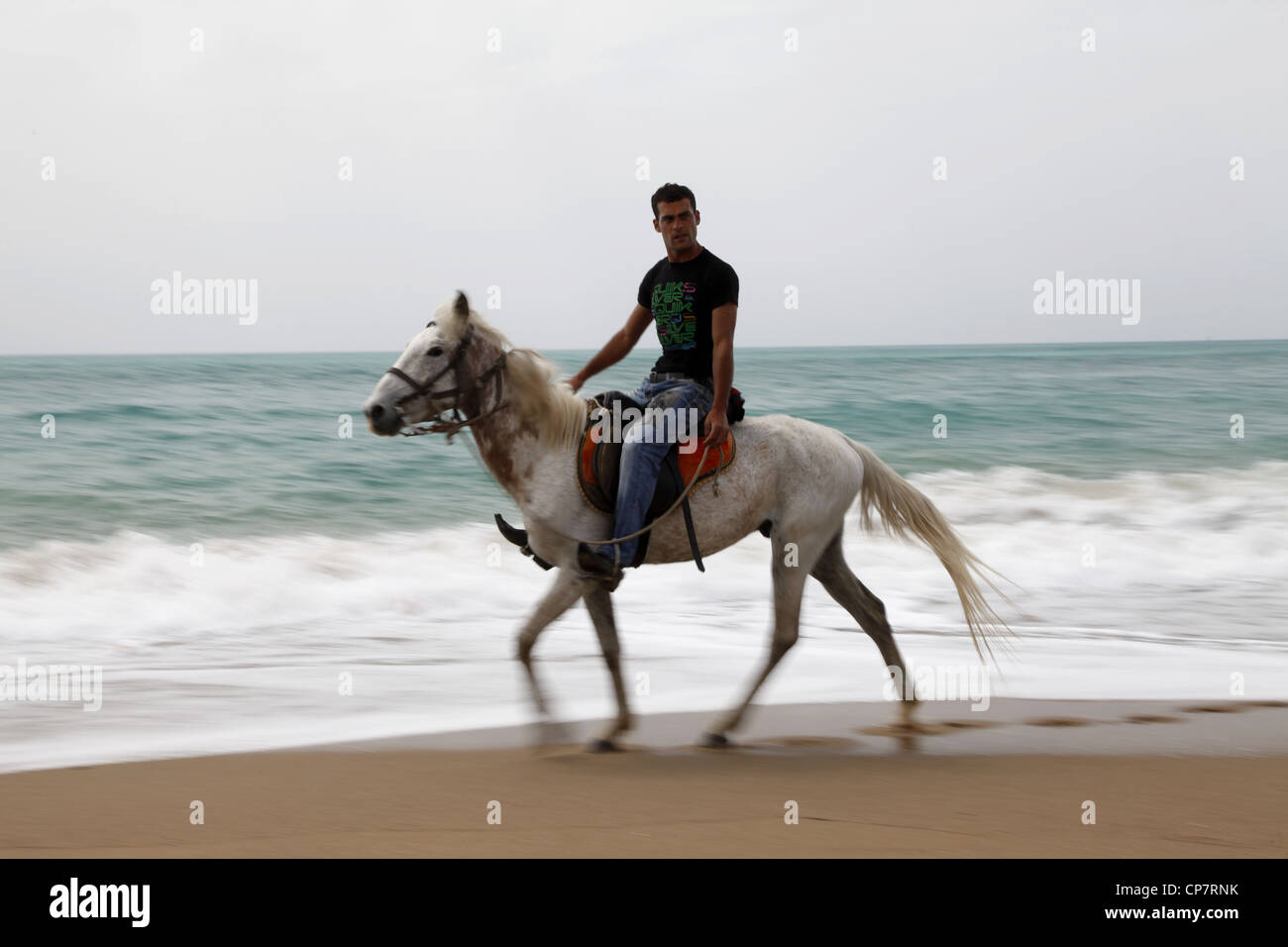 MAN ON WHITE HORSE MEDITERRANEAN COAST SIDE TURKEY 15 April 2012 - Stock Image