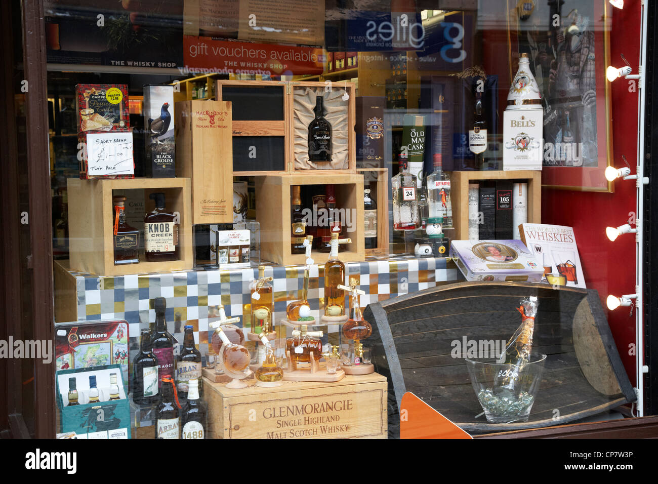 various bottles of scotch whisky in the window of a whisky shop in Fort William Scotland UK - Stock Image