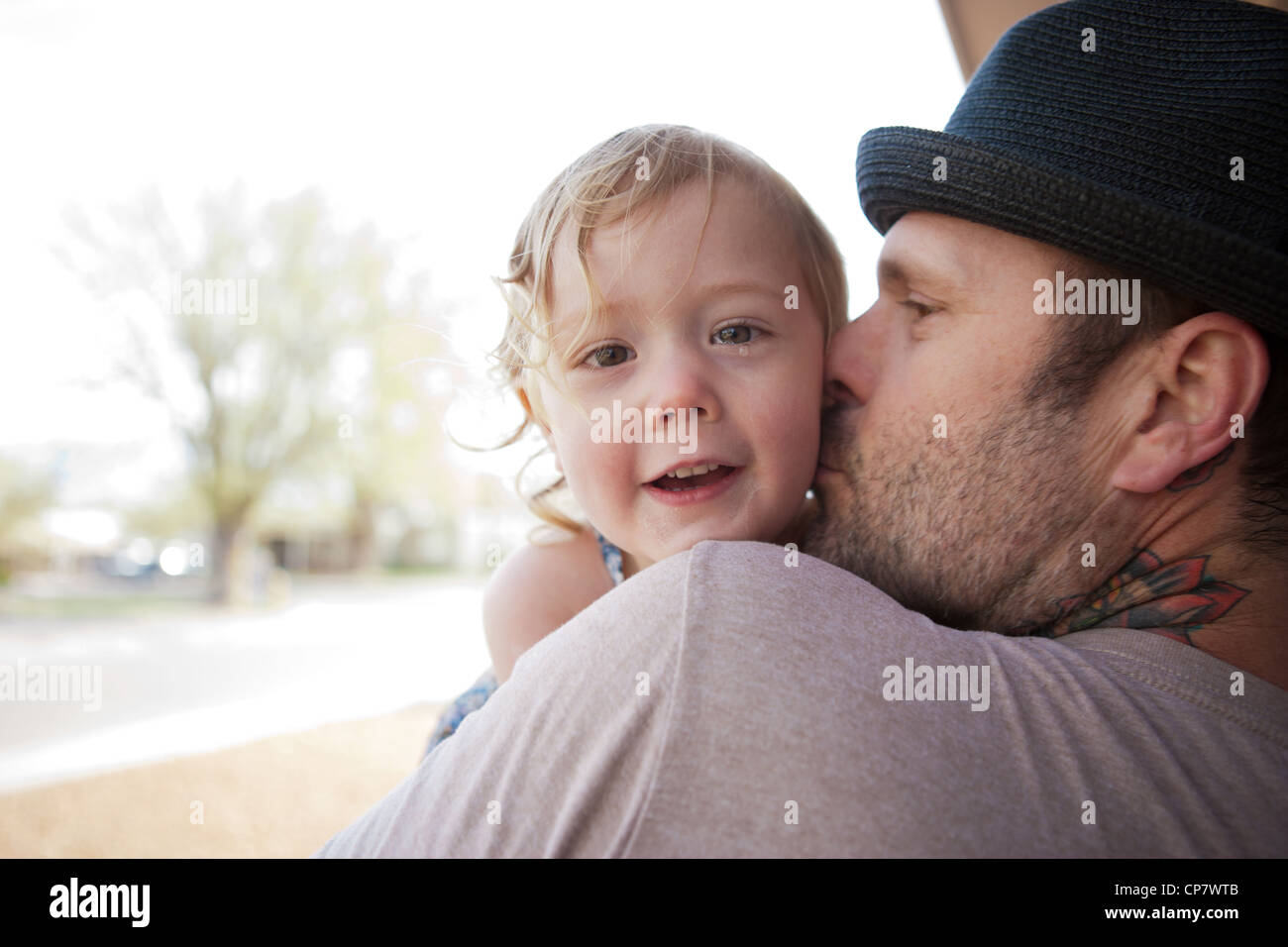Dad with tattoo on neck kisses two year old daughter. - Stock Image