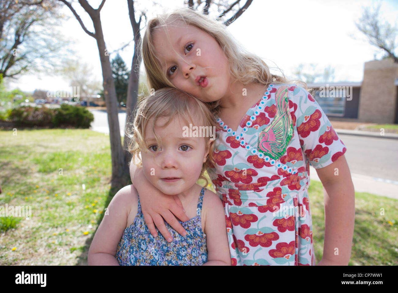 Sisters. age two and four, making silly faces hugging each other outdoors. - Stock Image
