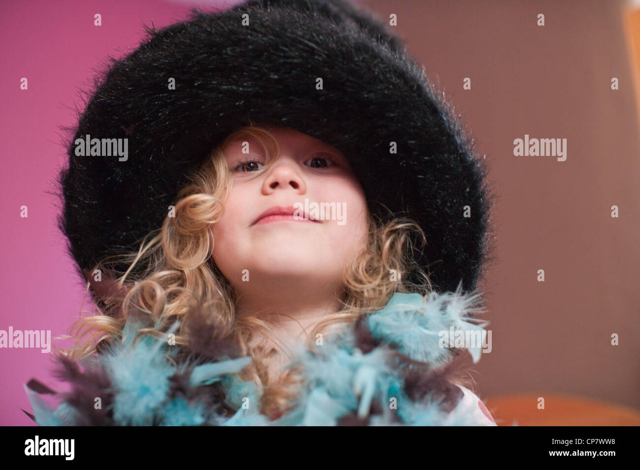Four year old girl tries on fancy costume hat and feather boa. - Stock Image