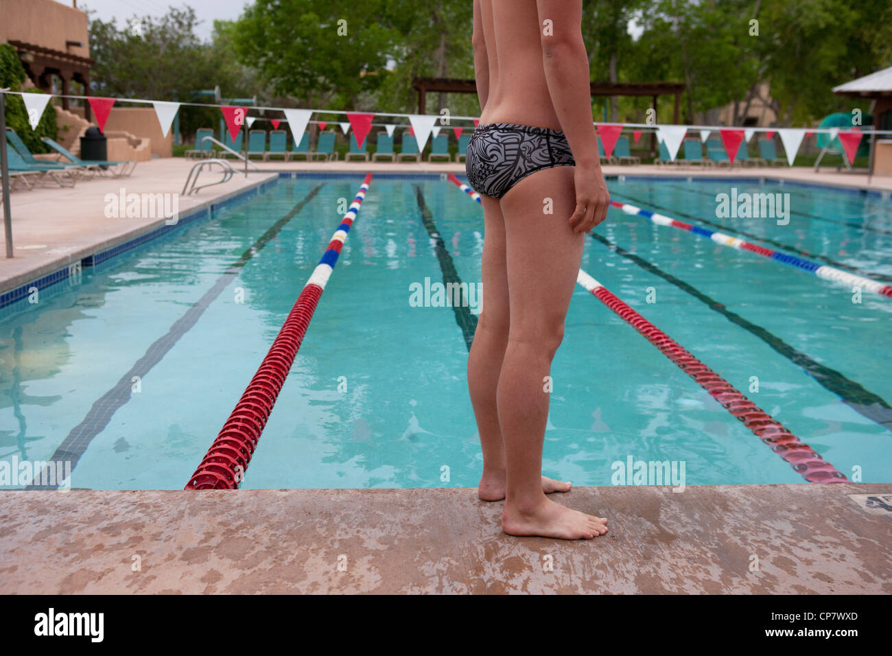 Swimmer taking a break and standing on the edge of the swimming pool. - Stock Image