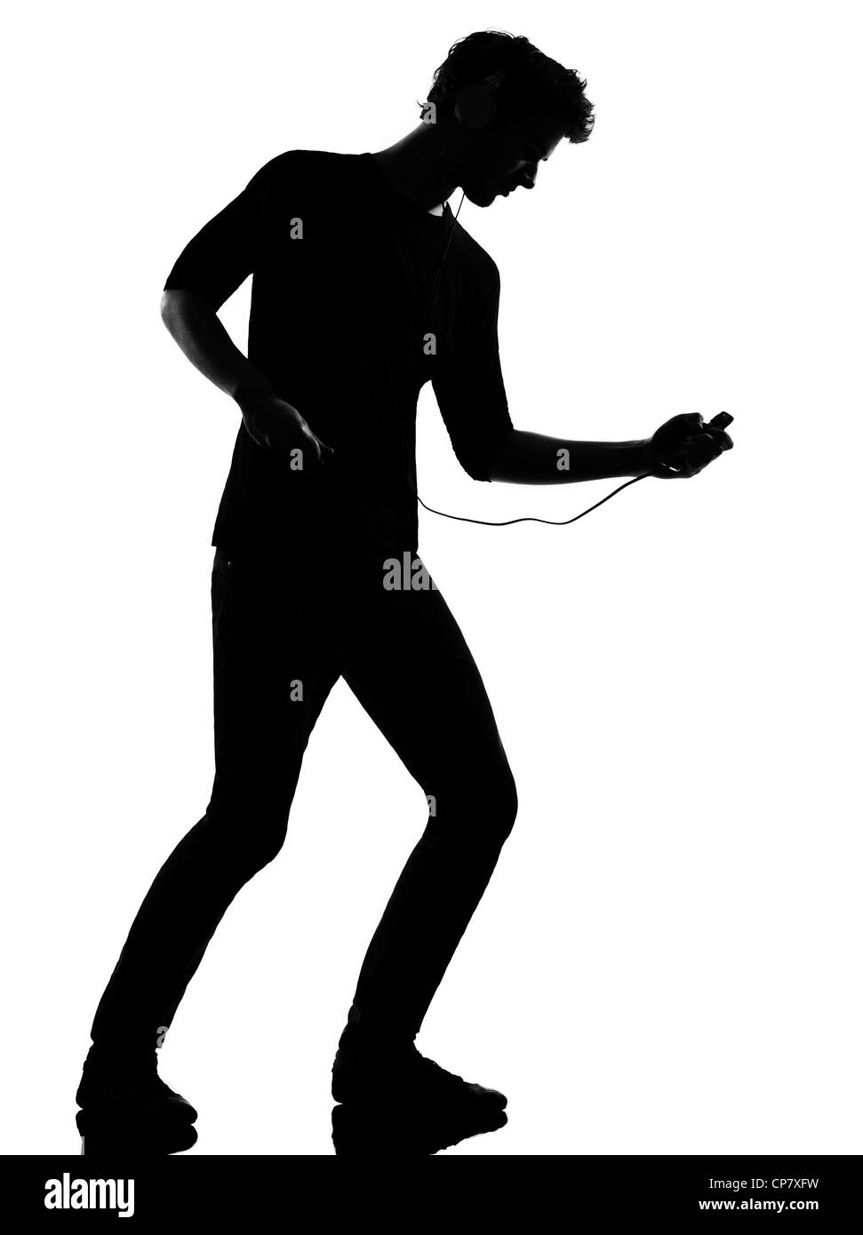 young man listening music audio player silhouette in studio isolated on white background - Stock Image