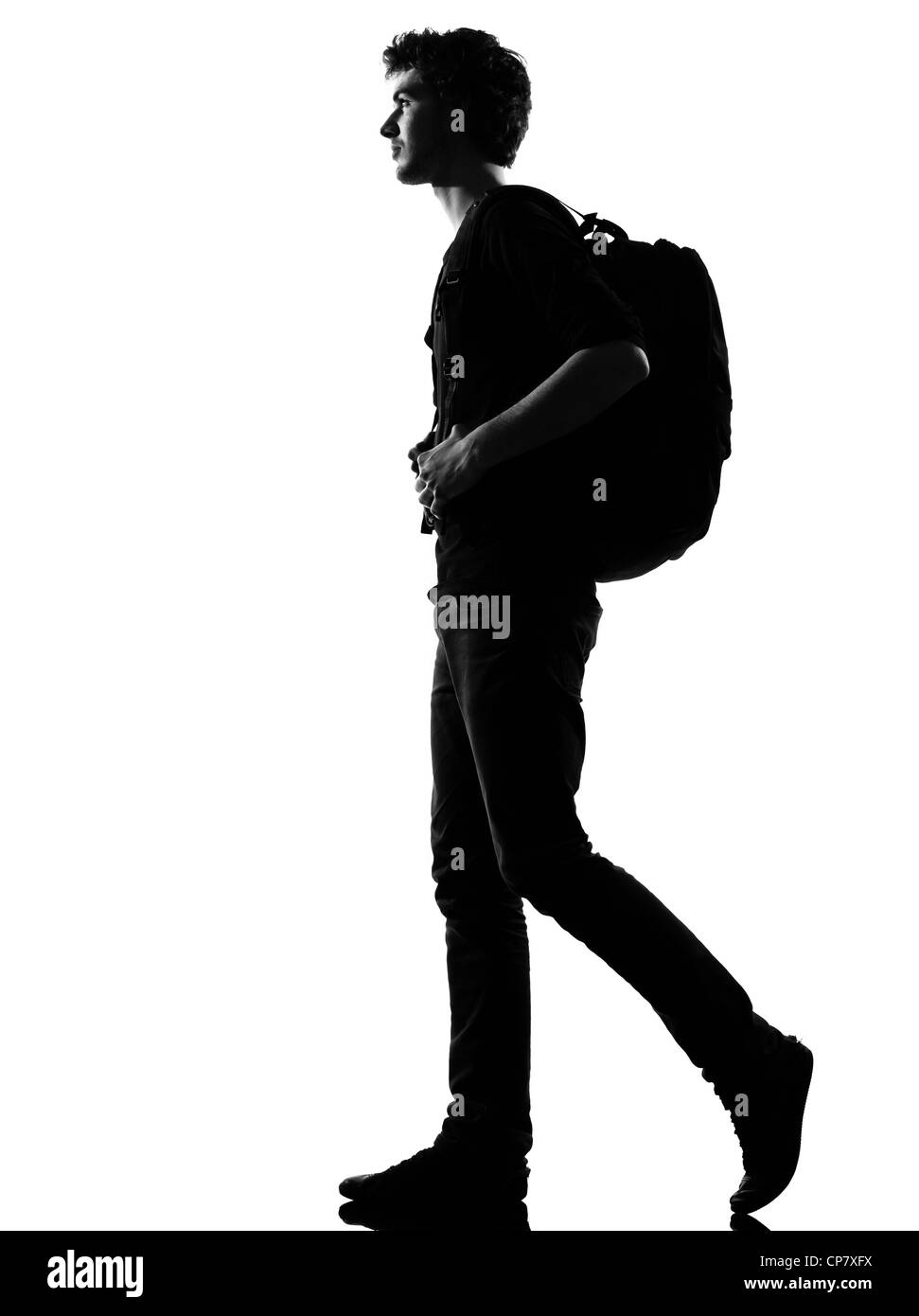 young man backpacker walking silhouette in studio isolated on white background - Stock Image