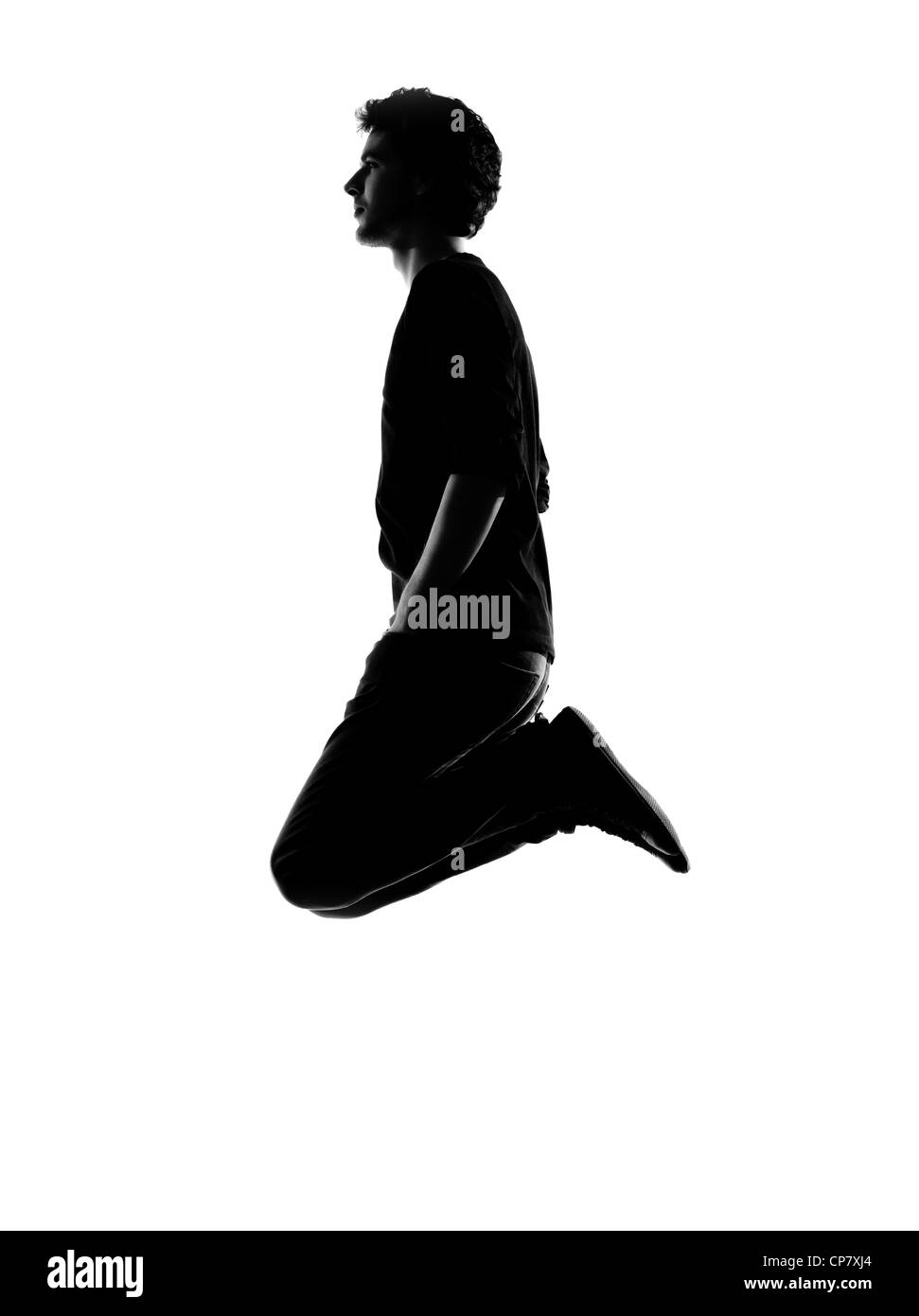 young man funny jumping silhouette in studio isolated on white background - Stock Image