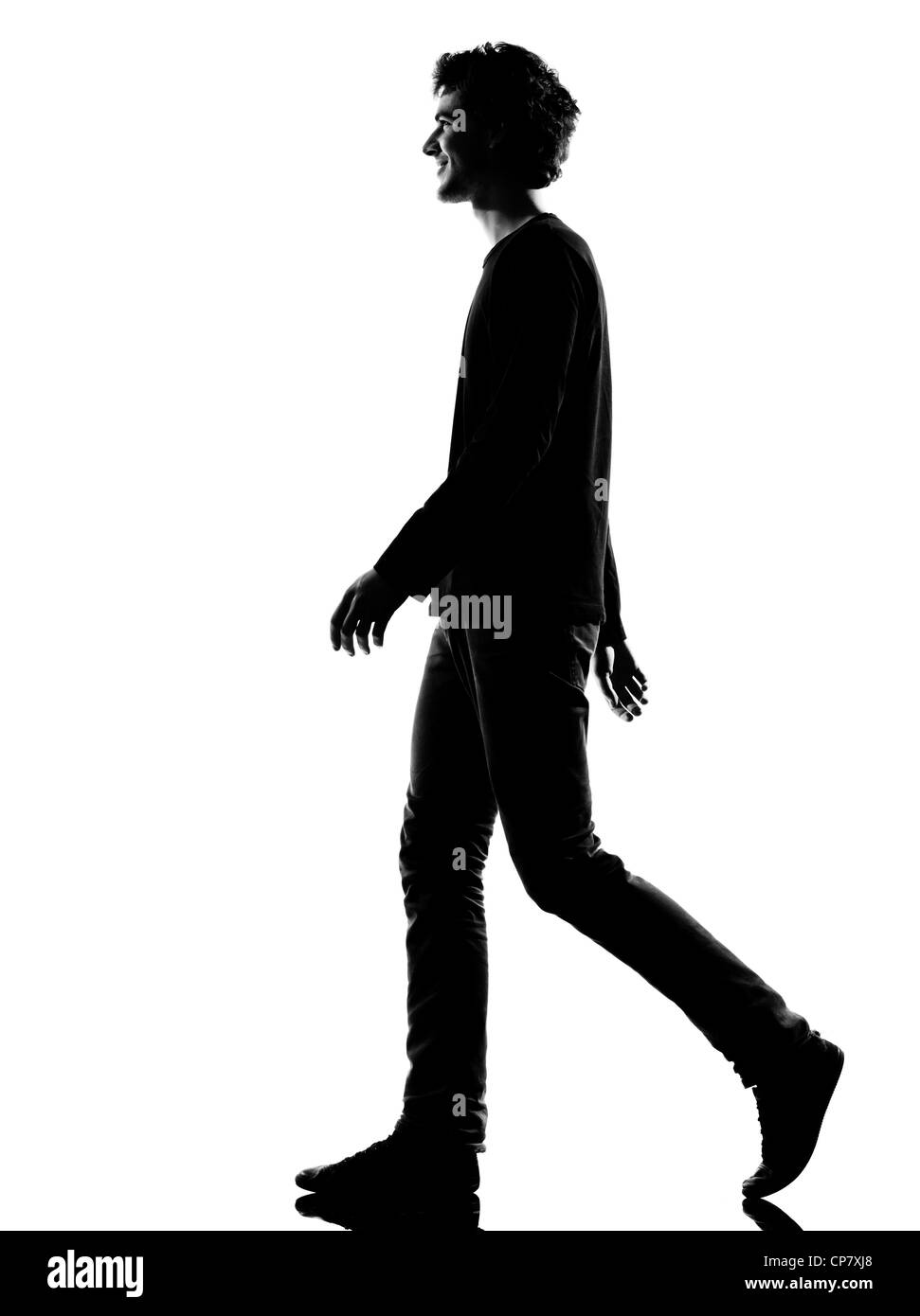 young man smiling walking silhouette in studio isolated on white background - Stock Image