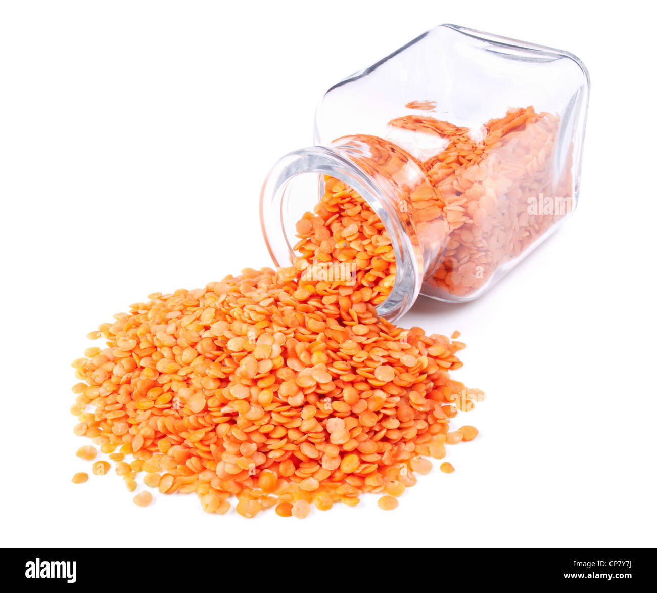 red split lentils scattered on a white background from glass jar - Stock Image