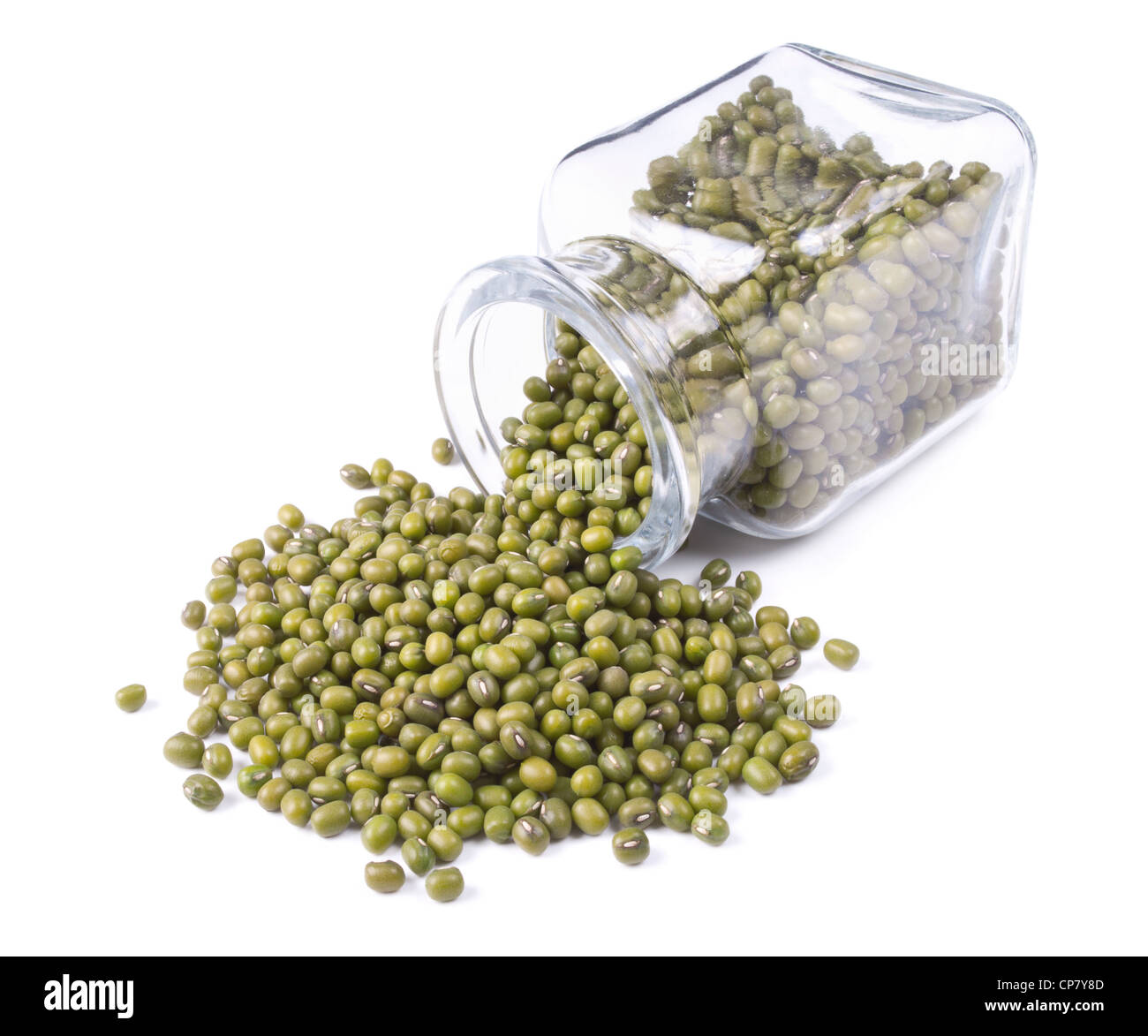 green mung scattered on a white background from glass jar - Stock Image