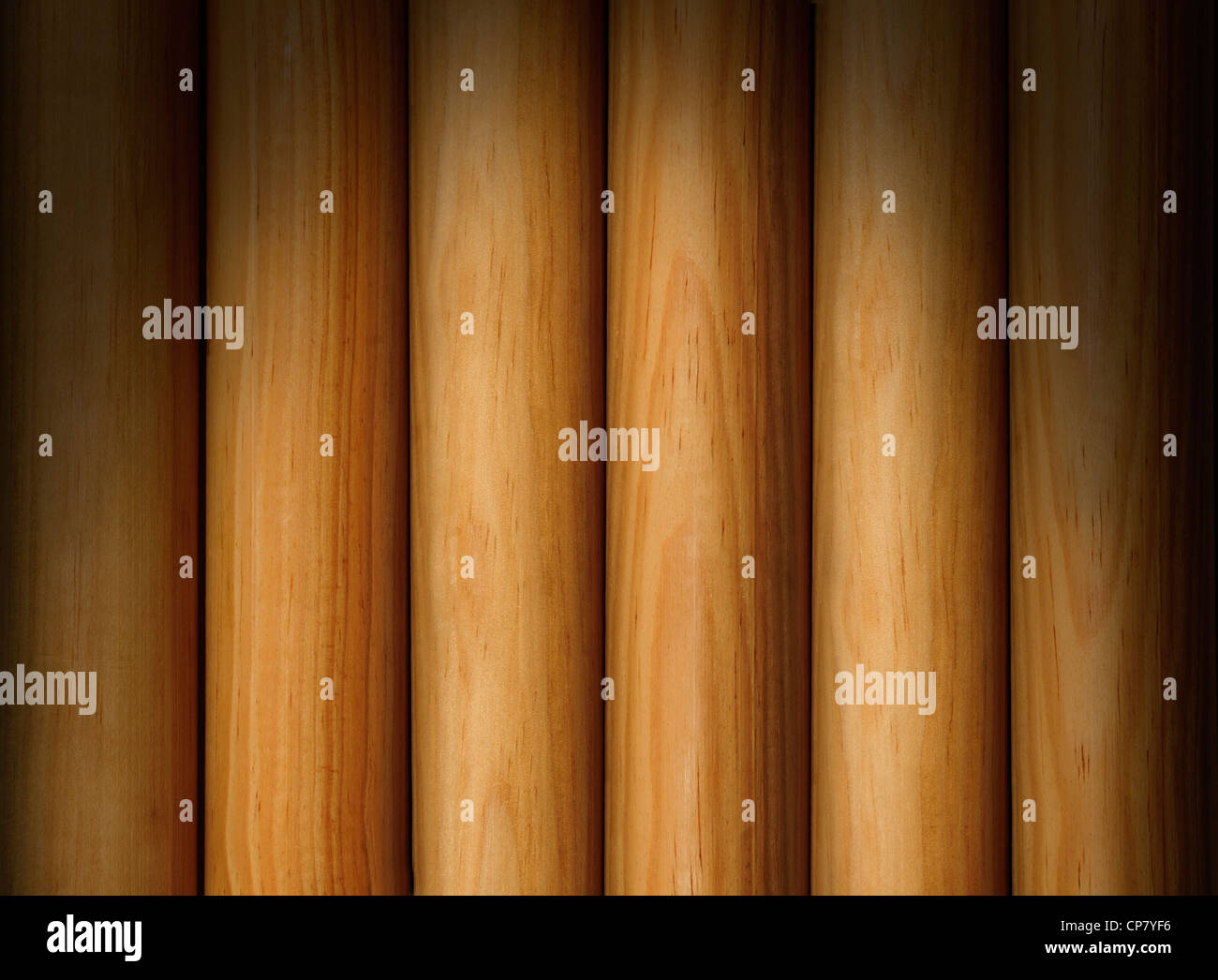 Wooden poles forming a background texture lit dramatically from above - Stock Image