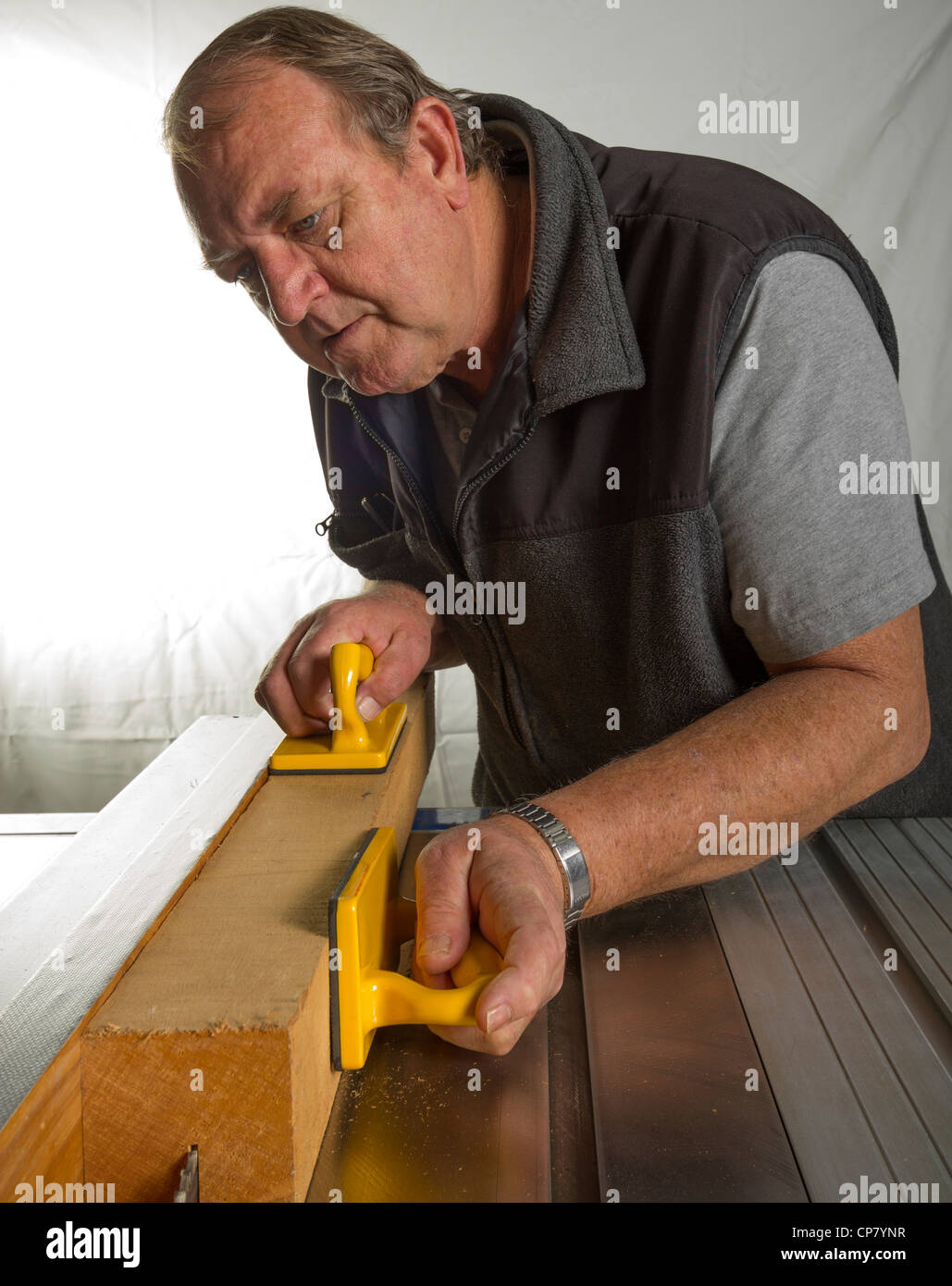 Senior male woodworker guiding a piece of wood through a saw bench machine in a workshop. - Stock Image